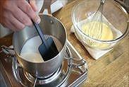 牛乳をゴムベラで混ぜながら加熱する