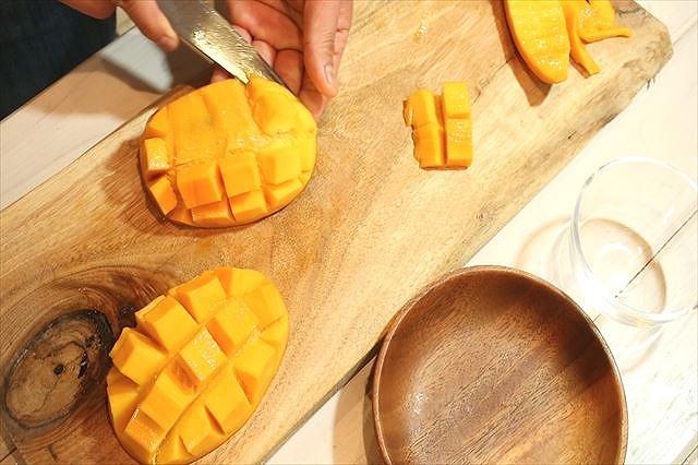 ダイヤモンドカットしたマンゴーの果肉を取る