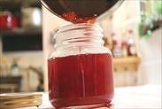 炊きあがったプラムジャムを保存瓶に流し入れる