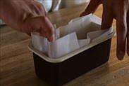 パウンドケーキ型用焼き紙をパウンドケーキ型に敷きこむ
