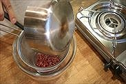 炊きあがったザクロのシロップをザルに入れる